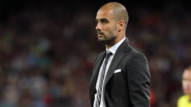 Picture of a suited Josep Guardiola observing a match from the touchline