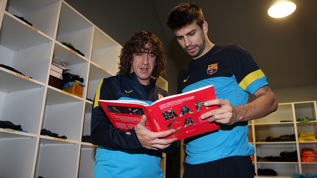 Gerard Piqu and Carles Puyol reading the book 'Bara. Orgullosos dels nostres colors' / FOTO: MIGUEL RUIZ - FCB