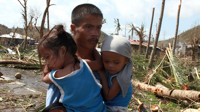 A philipinian man with his two children right after the typhoon