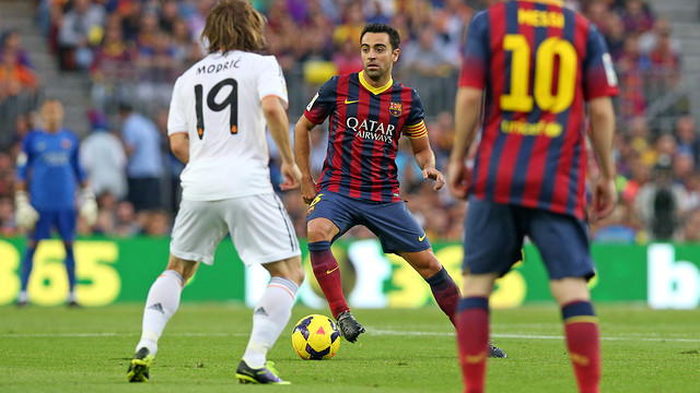 Xavi controls the ball in the match earlier this season against Real Madrid