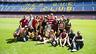 El grupo de jóvenes está rodeando la copa de la Champions en el césped del Camp Nou