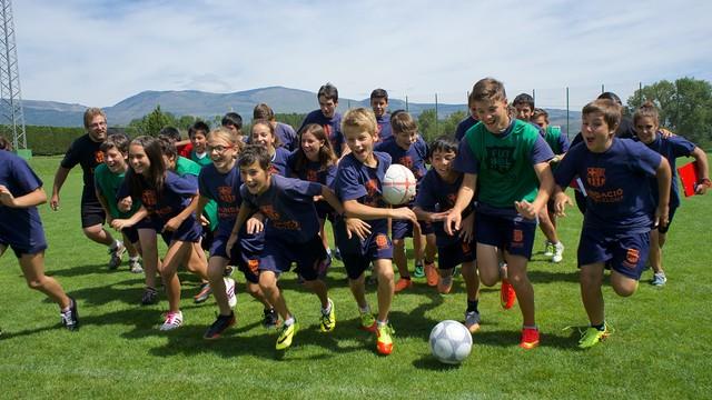 Un grup de nens corren en estampida sobre un camp de gespa.