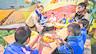 Unes educadores ofereixen higienitzant de mans a un grup de nens que atén un dels tallers de la campanya