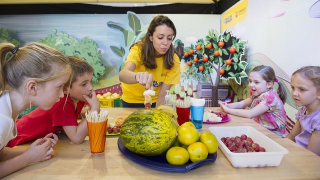 Un grup de nens miren unes fruites al taller d'alimentació saludable.