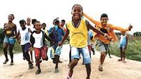 Un grup d'infants corre somrient cap a la càmera